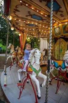 Leuk babymeisje op het paard van oude retro carrousel praag tsjechië