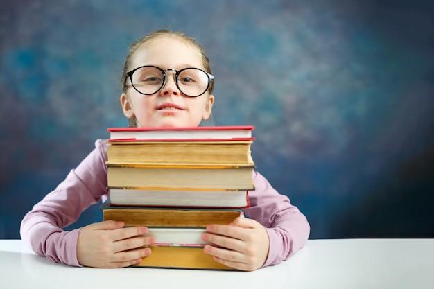 Leuk basisschoolmeisje met veel boeken
