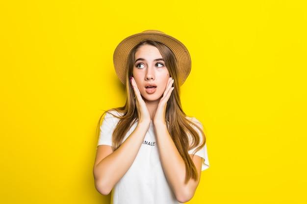 Leuk beschaamd model in wit t-shirt en hoed onder oranje achtergrond met grappig gezicht
