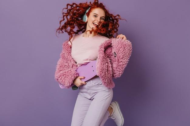 Leuk blauwogig meisje in roze jas en witte broek houdt longboard vast, luistert naar muziek met koptelefoon en springt op paarse ruimte.