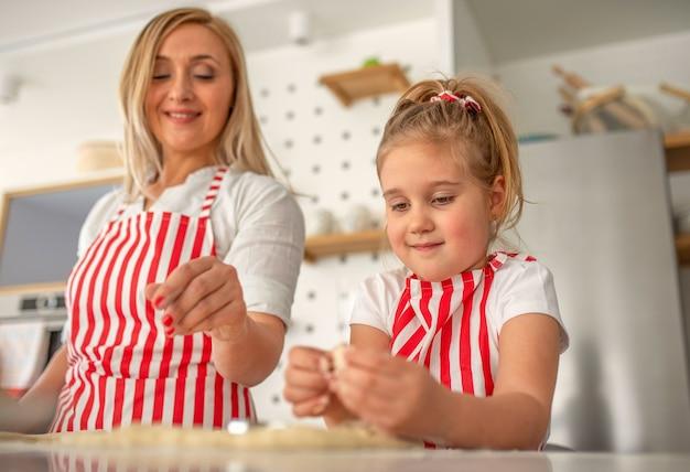 Leuk blond meisje dat gelukkig met haar moeder kookt