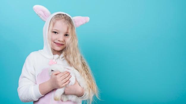 Leuk blond meisje in konijntjesoren met konijn