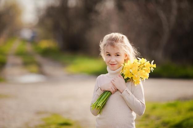 Leuk blonde gelukkig meisje met gele gele narcissen in het de lenteland