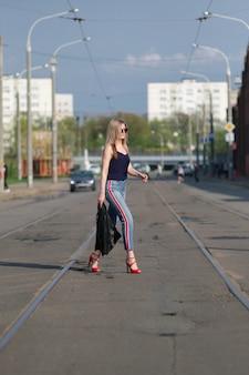 Leuk blondemeisje in zonnebril die de weg met in hand leerjasje kruisen