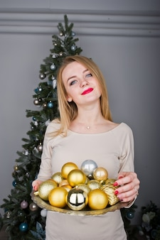 Leuk blondemeisje op beige kleding tegen nieuwe jaarboom met met gouden nieuwe jaarballen bij studio