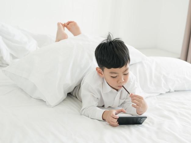 Leuk concentreerde weinig aziatisch jong geitje zich op smartphone terwijl het liggen op het bed