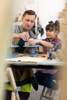 Leuk donkerharig meisje dat kleifiguren beeldhouwt met tekenleraar