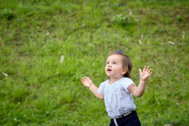 Leuk driejarig meisje dat met open armen naar de hemel kijkt en heel gelukkig.