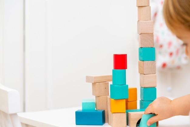Leuk en lief kind meisje thuis, spelen met houten bouwstenen speelgoed.