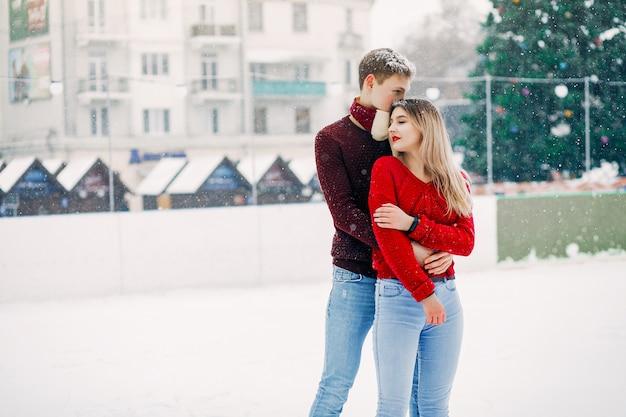 Leuk en liefdevol stel rode truien in een winterstad