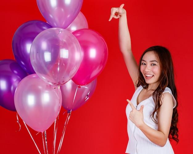 Leuk en mooi aziatisch meisje dat stinkt en speelt met kleurrijke luchtballonnen met een grappige en gelukkige glimlach op rode achtergrond, studiolichtopnamen festival en vieren concept.