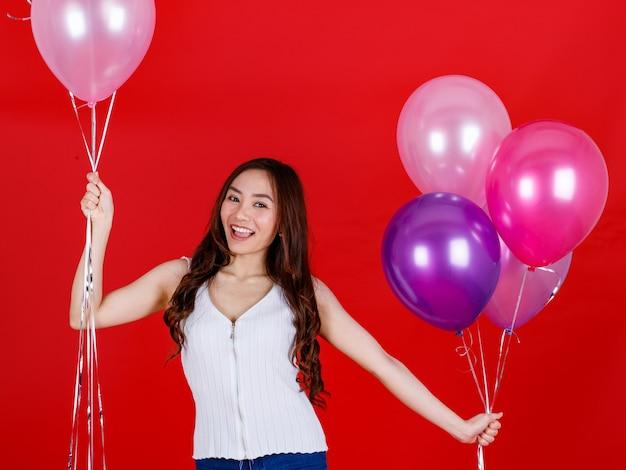 Leuk en mooi lang donker haar aziatisch meisje dat kleurrijke luchtballonnen vasthoudt en speelt met een grappige en gelukkige glimlach op rode achtergrond, studiolichtopnamen