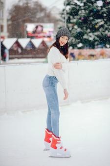Leuk en mooi meisje in een witte trui in een winterstad