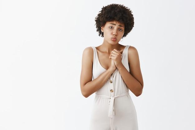 Leuk en timide stijlvol meisje poseren tegen de witte muur
