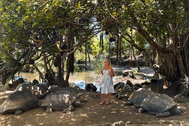 Leuk familie-entertainment op mauritius. een meisje staat in de buurt van reuzenschildpadden in de dierentuin van mauritius