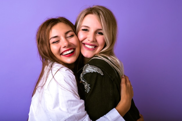 Leuk familieportret van de omhelzingen en de glimlach van twee zustervrouwen, levensstijl die portret, trendy hipsteroutfits, relatiesconcept, natuurlijke schoonheid, gelukkig samen bestuderen.