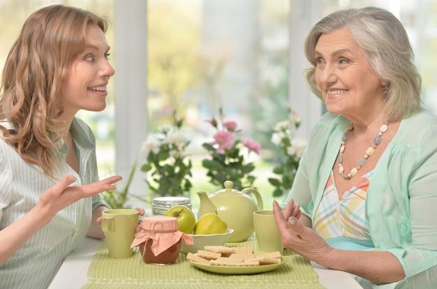 Leuk familieportret, volwassen dochter met senior ouders die thee drinken