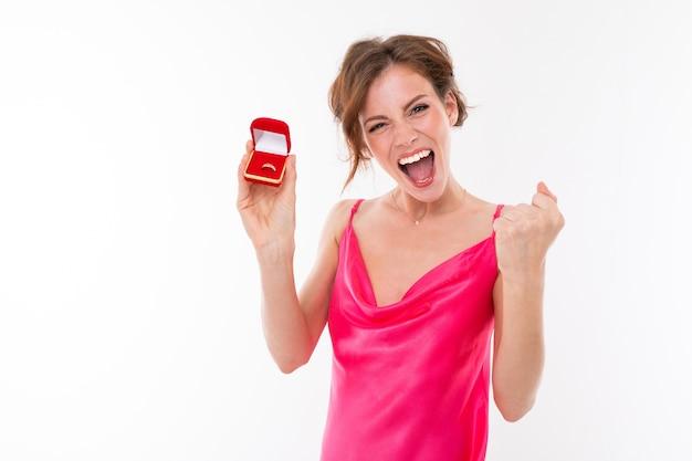 Leuk gelukkig emotioneel meisje met make-up in een roze jurk toont een doos met een ring op een witte achtergrond.