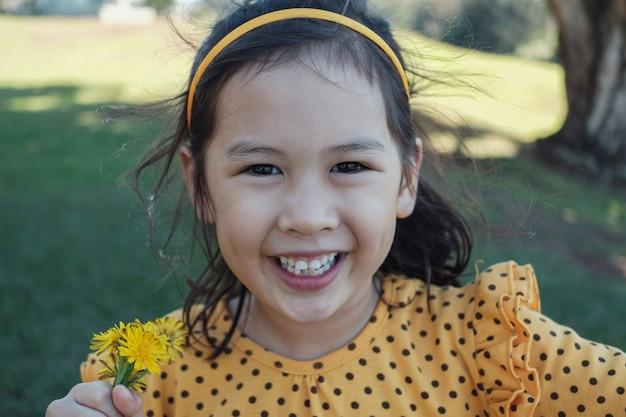 Leuk gelukkig en gezond gemengd meisje die het gele stip openlucht glimlachen dragen