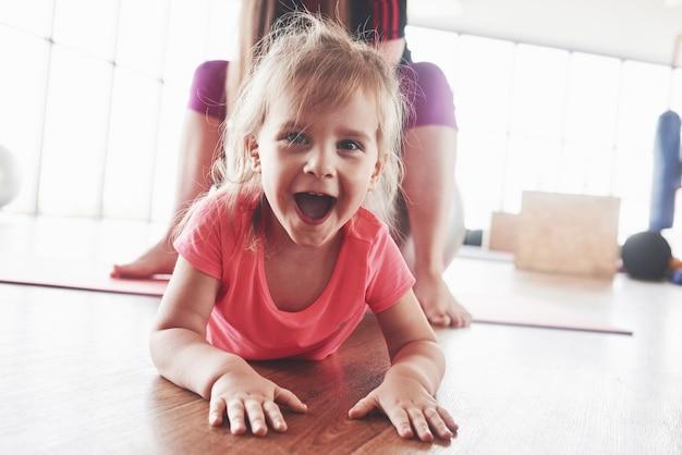 Leuk gelukkig jong meisje dat er recht uitziet en lacht met moeder die erachter zit.