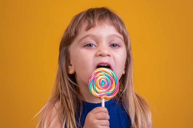 Leuk gelukkig kind met snoeplolly, gelukkig meisje dat grote suikerlolly eet, kind eet snoep. verrast kind met snoep. geïsoleerd op gele achtergrond, studio. mooi klein meisje met lolly