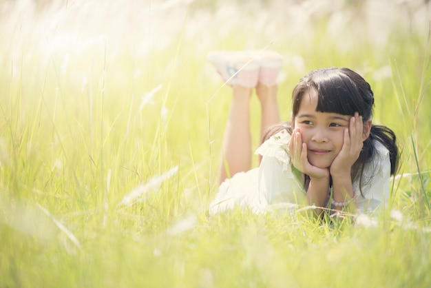 Leuk gelukkig meisje dat op gras ligt.