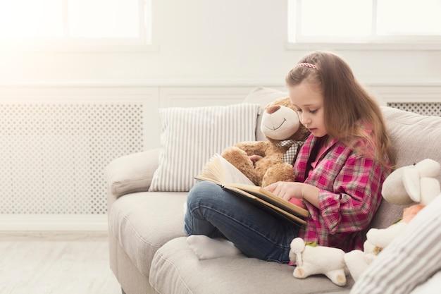 Leuk gelukkig meisje dat teddybeer omhelst en boek leest. mooi kind thuis, zittend op de bank met haar favoriete speelgoed, plezier hebben, ruimte kopiëren