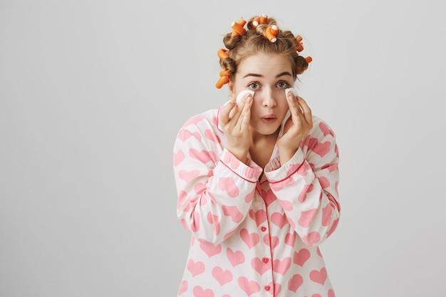 Leuk gelukkig meisje in nachtkleding en haarkrulspelden afvegen make-up met wattenschijfjes