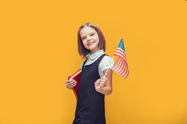Leuk glimlachend kaukasisch schoolmeisje dat amerikaanse vlag en boek op gele achtergrondvlag houdt
