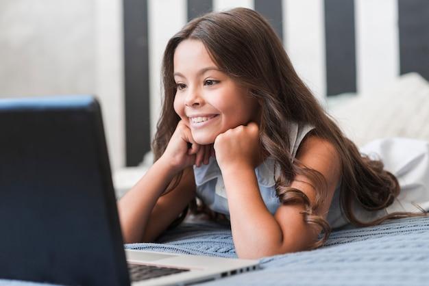 Leuk glimlachend meisje die op bed het letten op video op laptop liggen