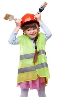 Leuk glimlachend meisje in beschermende bouwhelm en vest die rond met verfborstels op wit geïsoleerde achtergrond voor de gek houden