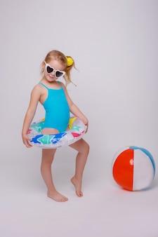 Leuk glimlachend meisje in zwempak met rubberring dat op wit wordt geïsoleerd