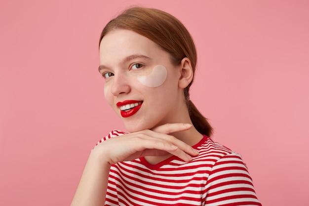 Leuk glimlachend roodharig meisje draagt een rood gestreept t-shirt, met rode lippen en met vlekken onder de ogen, raakt de kin, staat en geniet van vrije tijd voor huidverzorging.