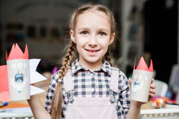 Leuk glimlachend schoolmeisje dat enge halloween-speelgoed toont dat uit opgerold papier door haarzelf bij les wordt samengesteld
