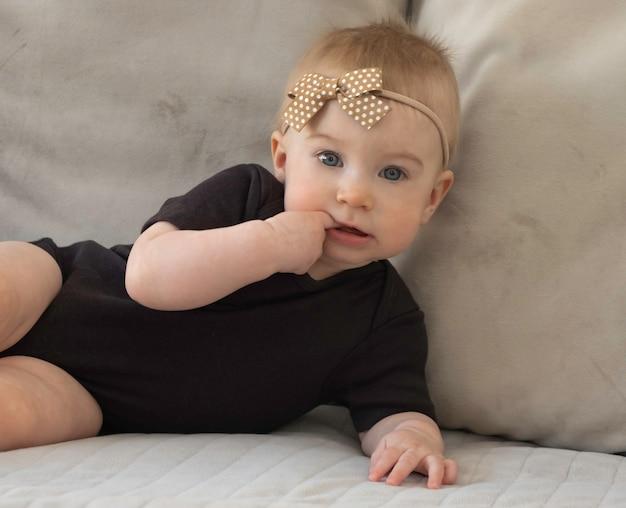 Leuk grappig kaukasisch blond babymeisje met bruin bowlying op bank vingers in de mond brengen