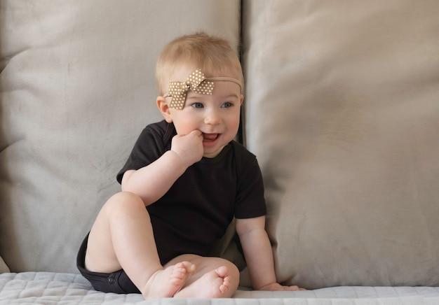 Leuk grappig kaukasisch blond babymeisje, zittend op het oppervlak van beige bankkussens in zwart lichaam met bruine strik