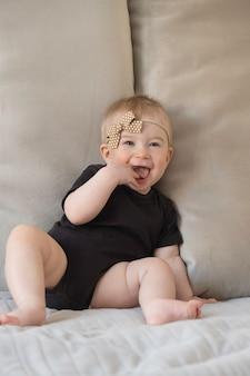 Leuk grappig kaukasisch blond babymeisje, zittend op het oppervlak van beige bankkussens in zwart lichaam met bruine strik Premium Foto