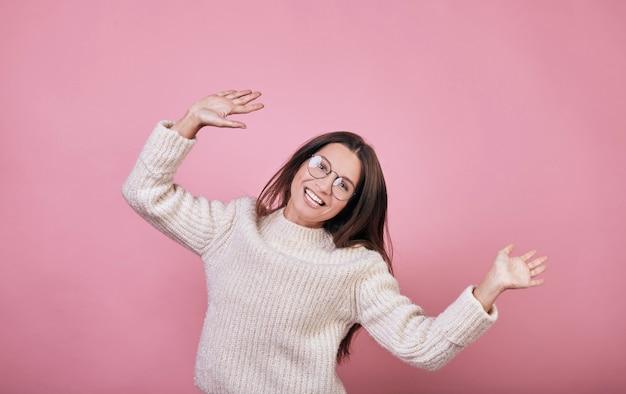 Leuk grappig meisje dat in sweater met glimlach springt
