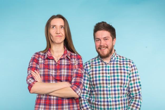Leuk grappig paar in geruite overhemden die op blauw lachen