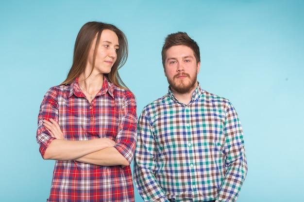 Leuk grappig paar in geruite overhemden die op blauwe achtergrond lachen