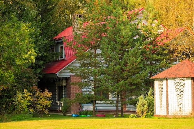 Leuk huis met rood dak in bos omgeven door bomen mooie herfst zonnige dag een vakantiehuis v...
