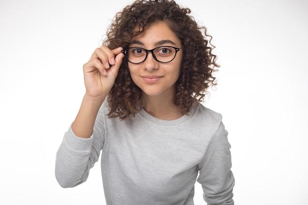 Leuk indisch donkerbruin meisje dat met glazen de camera bekijkt. portret van een mooie gemengd ras vrouw.