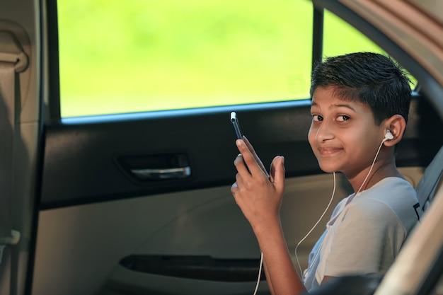 Leuk indisch kind dat in auto zit en slimme telefoon en hoofdtelefoonsgadget gebruikt
