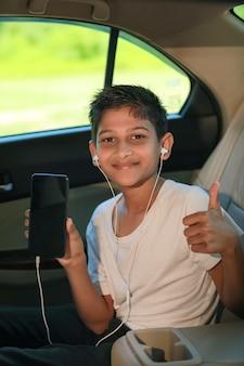 Leuk indisch kind dat slimme telefoon met dreunen in autoraam toont