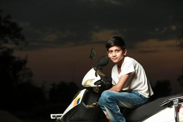 Leuk indisch klein kind dat op autoped zit en meerdere uitdrukking geeft