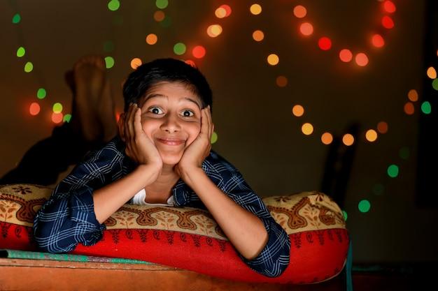 Leuk indisch klein kind dat uitdrukking over verlichtingsruimte toont