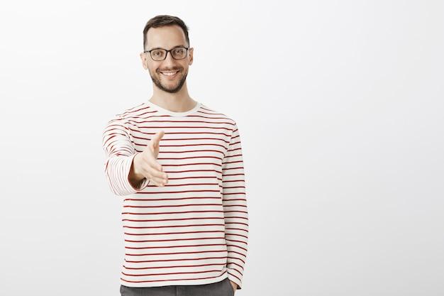 Leuk je te ontmoeten. portret van vriendelijke zelfverzekerde volwassen zakenman in gestreepte trui, hand in handdruk trekken en vreugdevol glimlachend, staande over grijze muur
