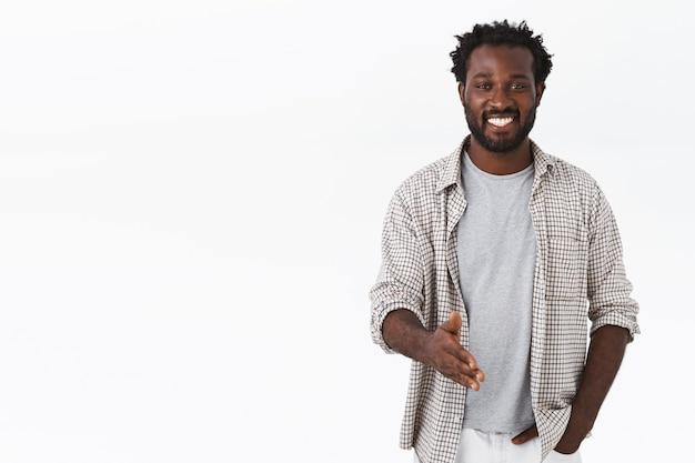 Leuk je te ontmoeten. vrolijke afro-amerikaanse bebaarde man strek arm voor handdruk om iemand te begroeten
