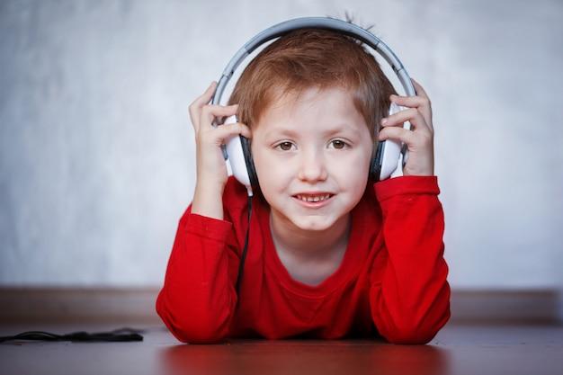 Leuk jong geitje dat aan muziek op hoofdtelefoons luistert en geniet van