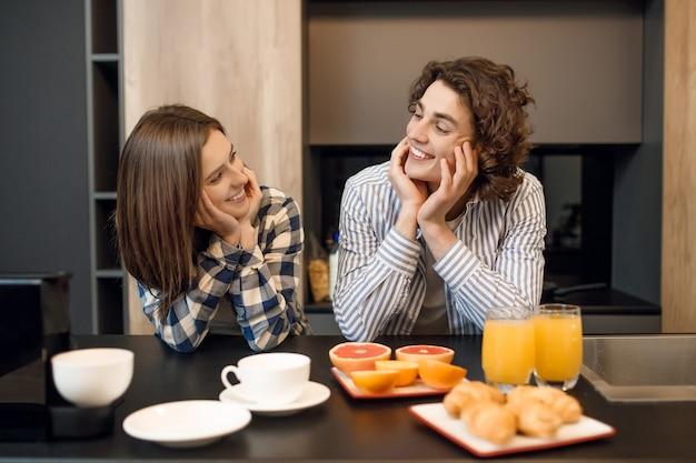 Leuk jong getrouwd stel dat samen geniet van hun ontbijt in de vroege ochtend.